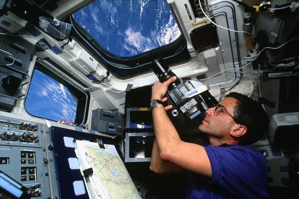 Astronaut Filming Through the Window of a Space Shuttle