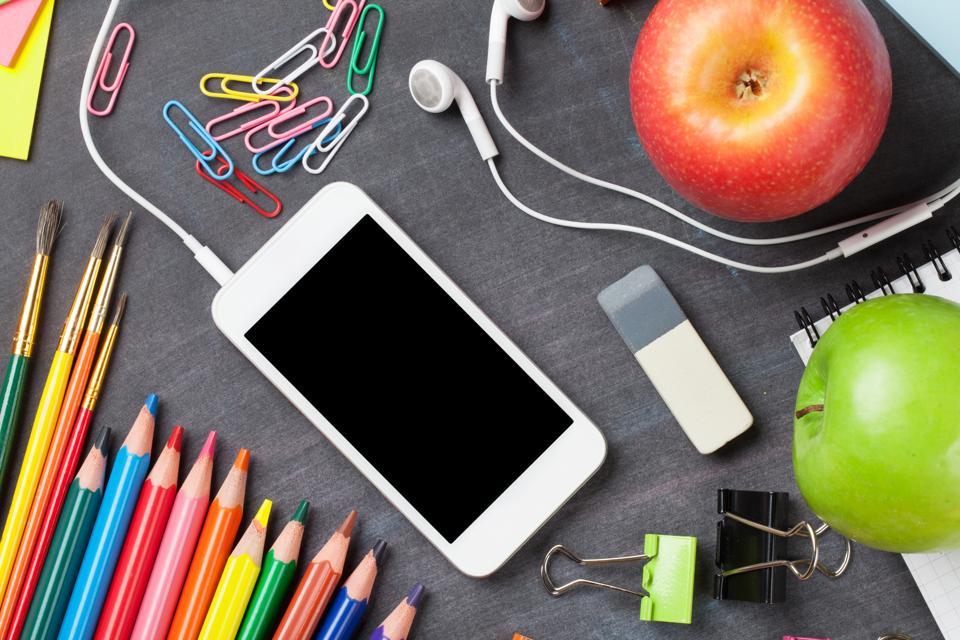 School supplies and smartphone on blackboard background