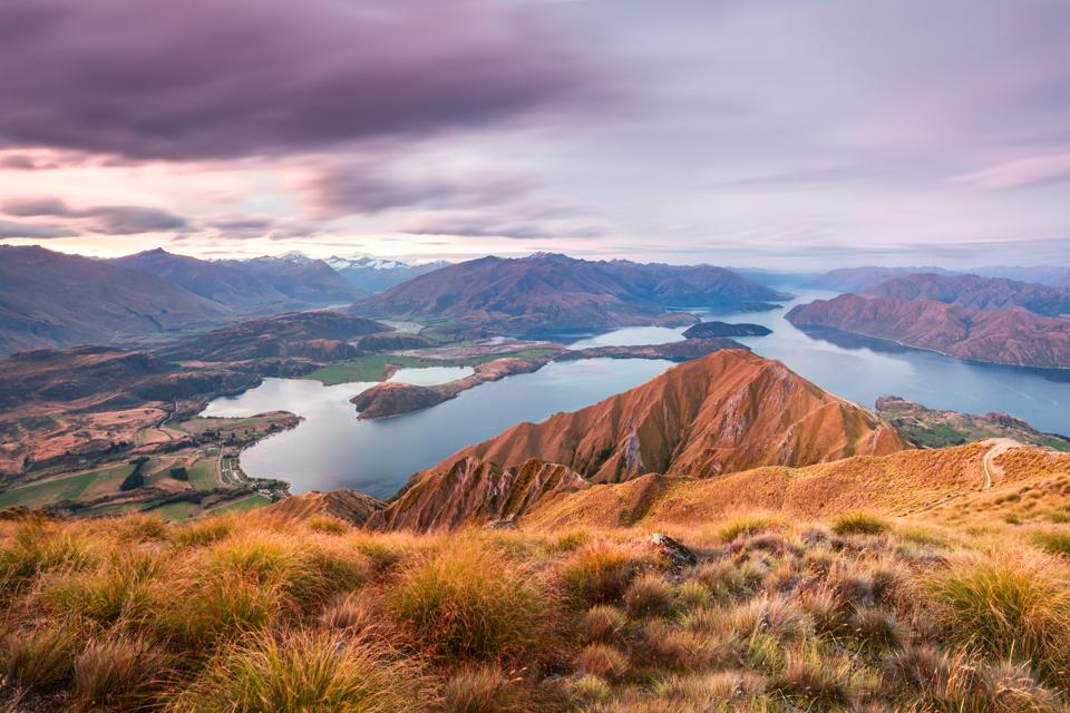 The sun sets over the lake and mountains of Wanaka, New Zealand