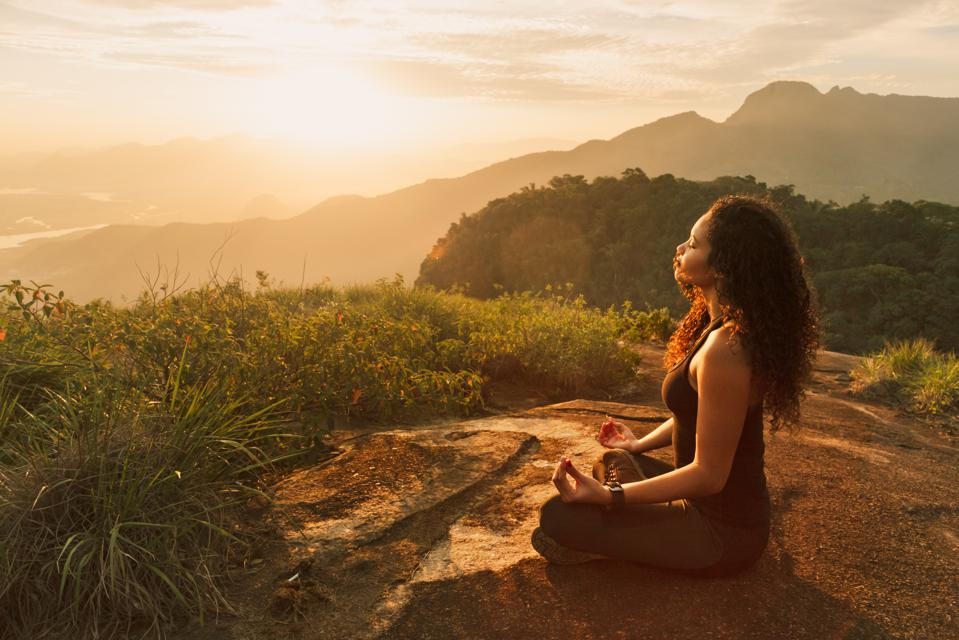 Young woman meditating on mountain top