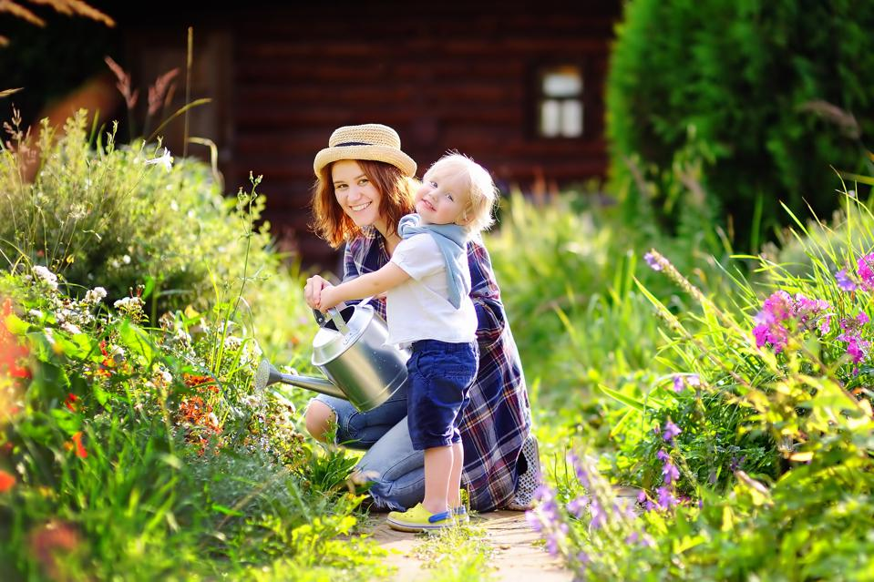 Toddler boy and his mother watering plants in the garden