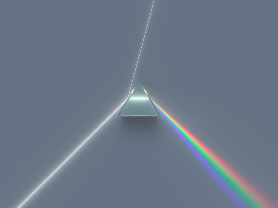 Light passing through a dispersive prism and separating into clearly defined colors.