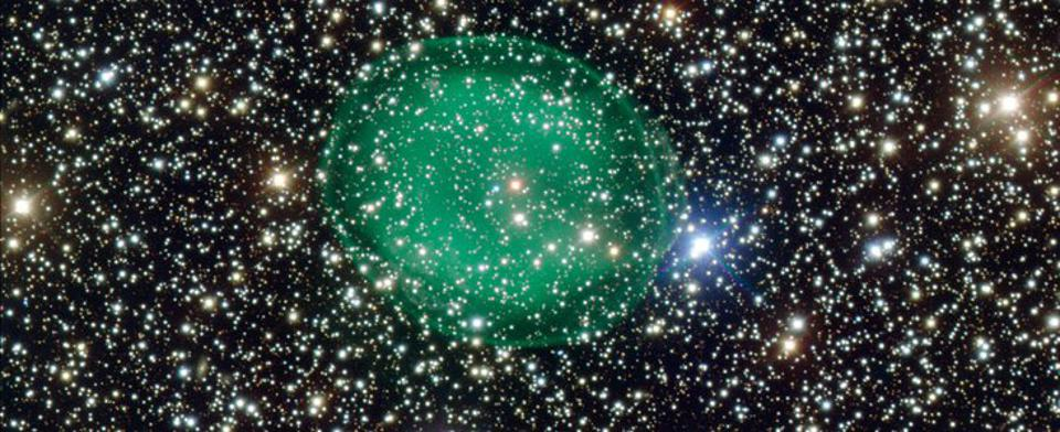The glowing green planetary nebula IC 1295 surrounding a dim and dying star.