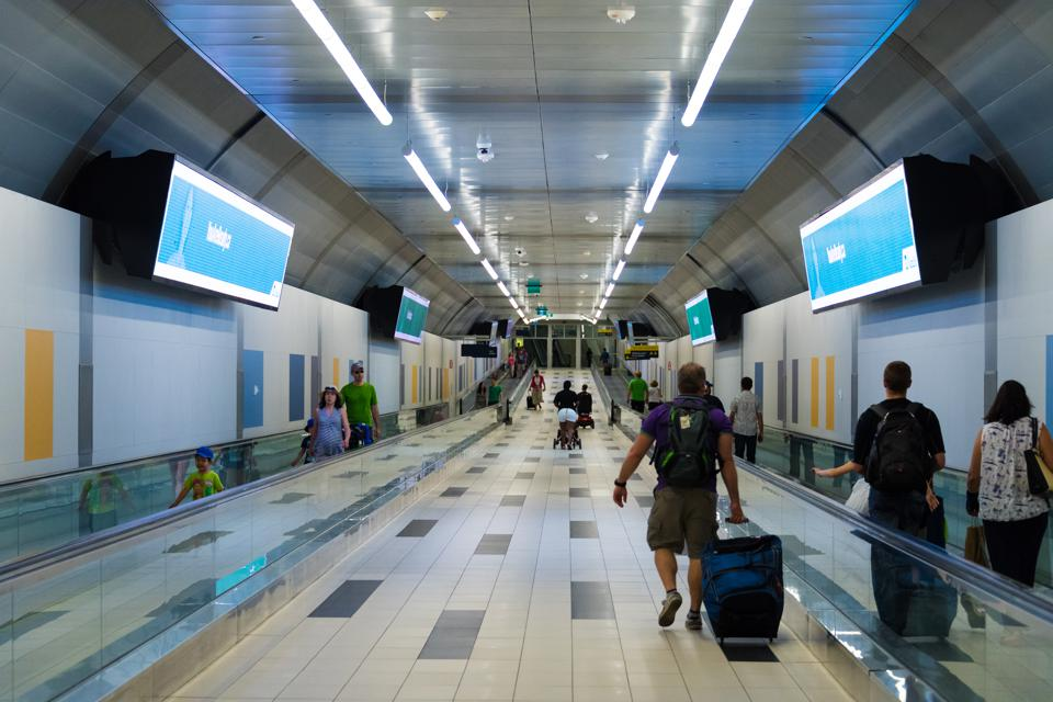 Billy Bishop airport tunnel. Travelers carrying their...