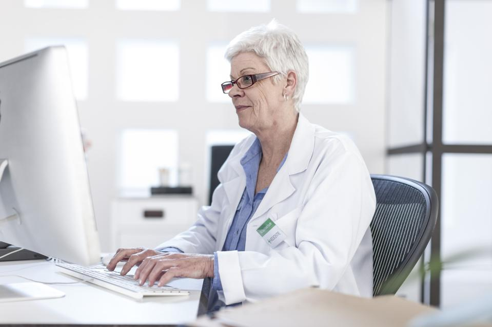 Senior woman in lab coat working on computer