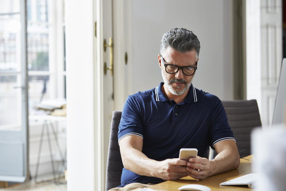 Businessman using mobile phone at desk