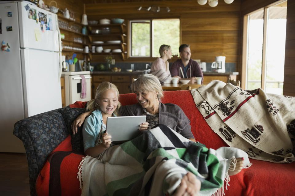 Grandmother and granddaughter using digital tablet cabin sofa