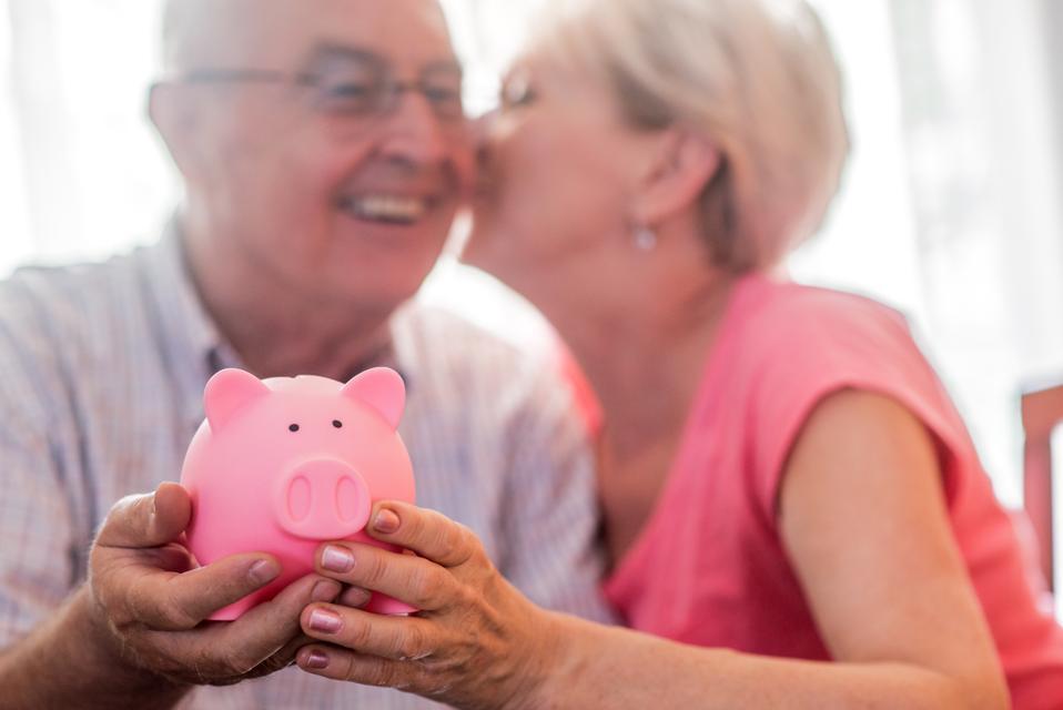 Retirement savings for senior couple, holding piggy bank