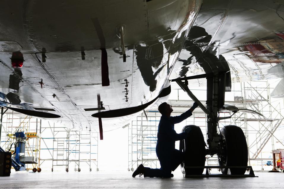 Engineer inspecting landing on gear on passenger jet in hangar