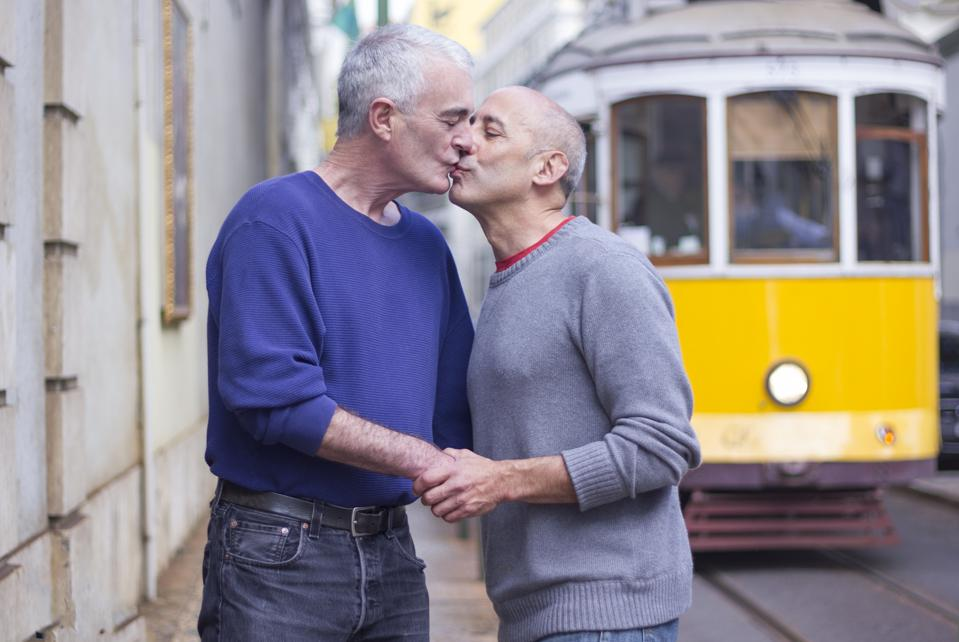Senior Gay Male Couple Kissing in Front of Trolley