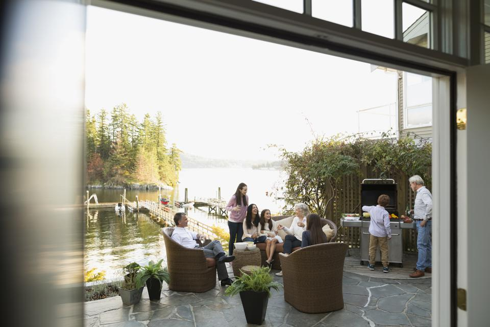 Multi-generation family barbecuing and relaxing lakeside patio