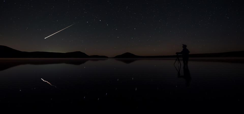 A bright meteor flying past the Big Dipper reflected on a lake.