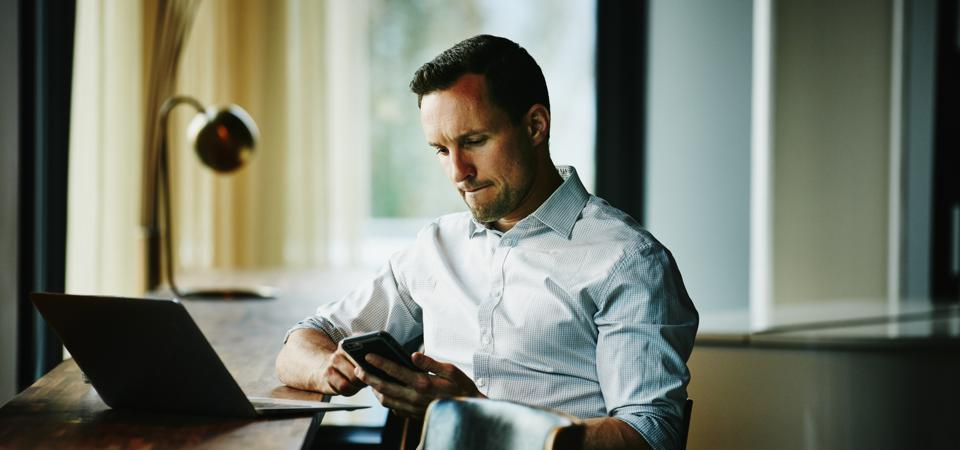 Businessman looking at smartphone in office