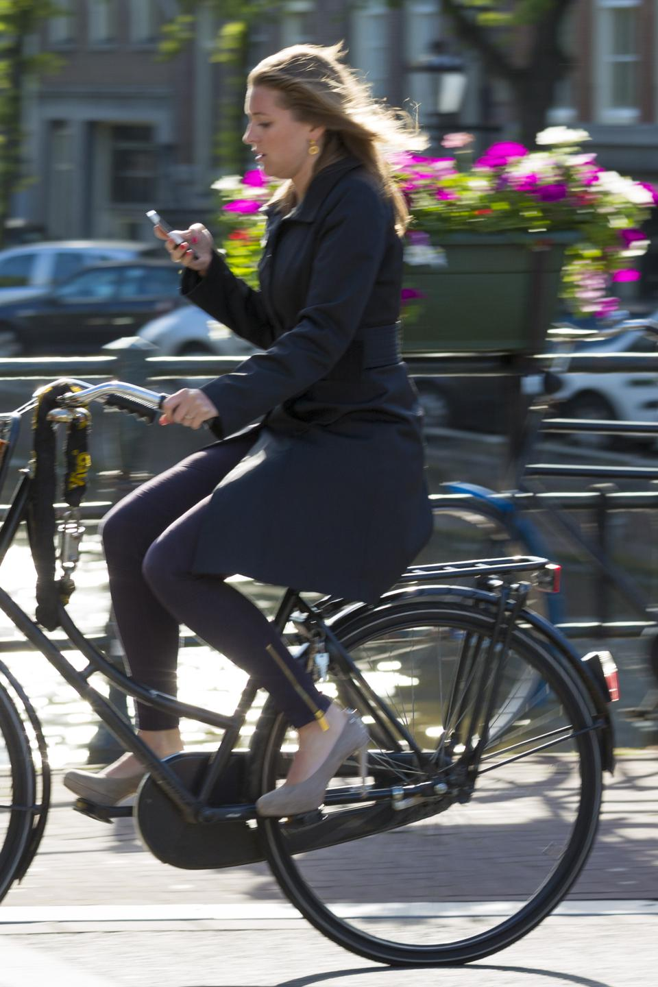Woman texting while on moving bicycle