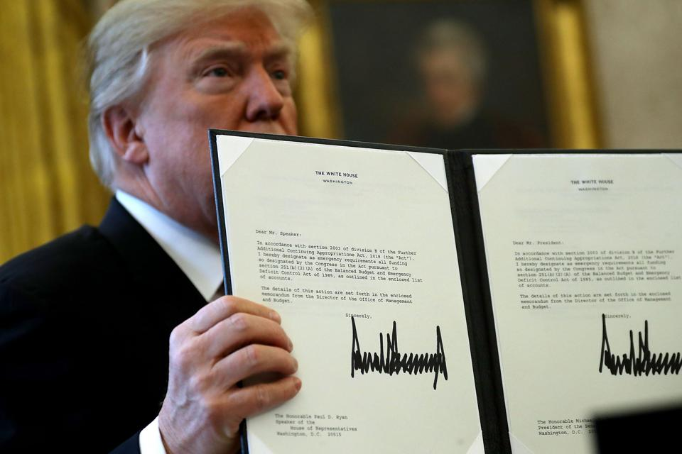 Donald Trump signs the new law at the White House.