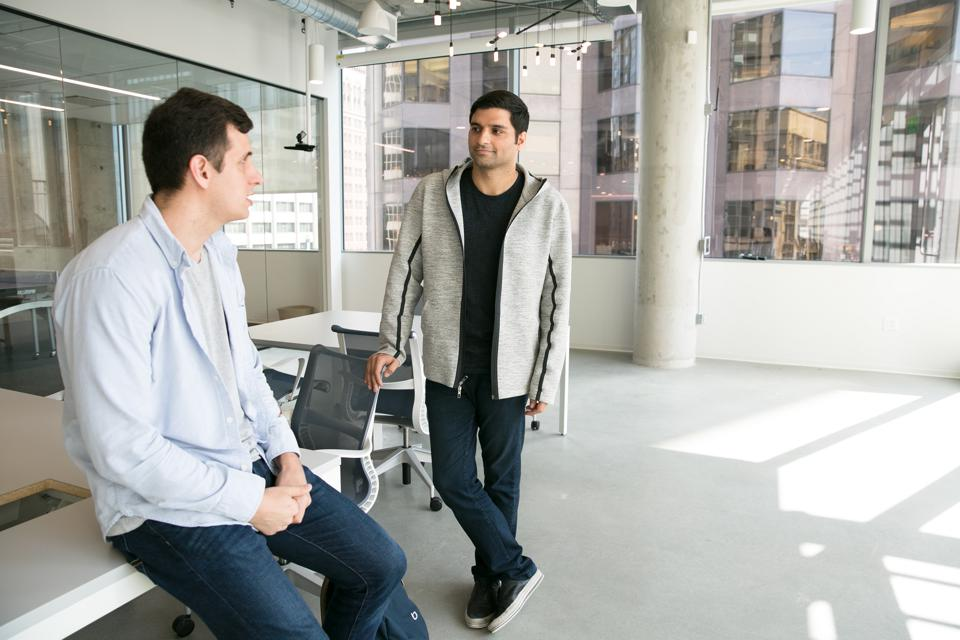 Blend CEO Nima Ghamsari (right) speaking with an employee.