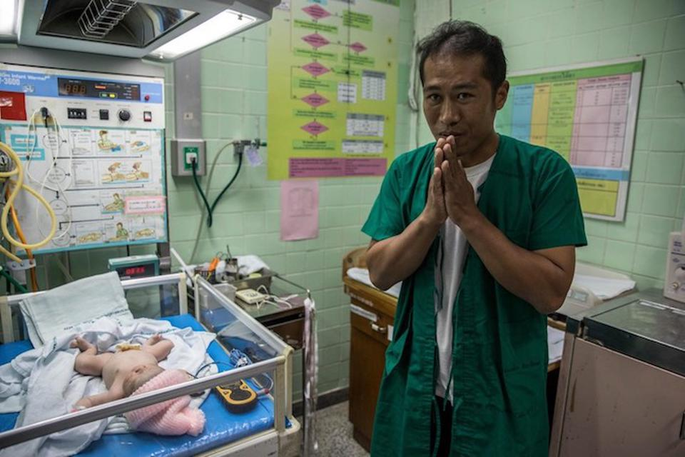 Sai Tlen, 38, meets his newborn daughter, born via cesarean section at the Health Promotion Center Region 1 in Thailand's Chiang Mai Province.