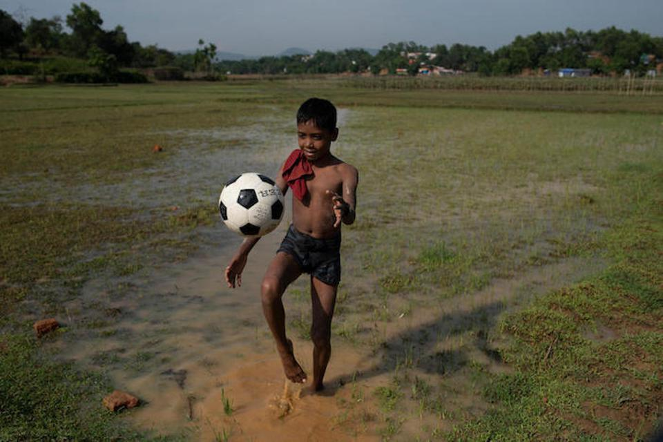 After a heavy rain that saturated the ground, Hafizul Mustafa, 11, a Rohingya refugee from Myanmar, plays soccer in Balukhali camp, Cox's Bazaar District, Bangladesh in May 2018.