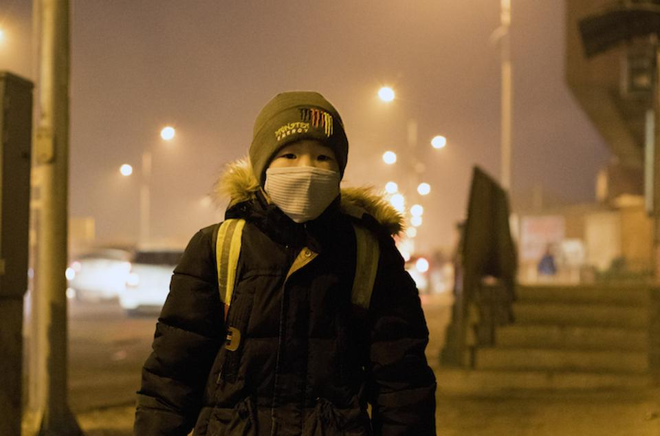 A young boy waits for the school bus in Songinokhairkhan district of Ulaanbaatar, the capital city of Mongolia, where air pollution levels are dangerously high, resulting in a public health crisis for children.