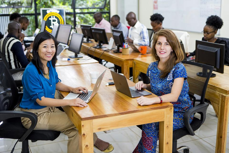BitPesa COO Charlene Chen and CEO Elizabeth Rossiello sit in the company's Nairobi office with its East Africa team. BitPesa's staff is 50% female.