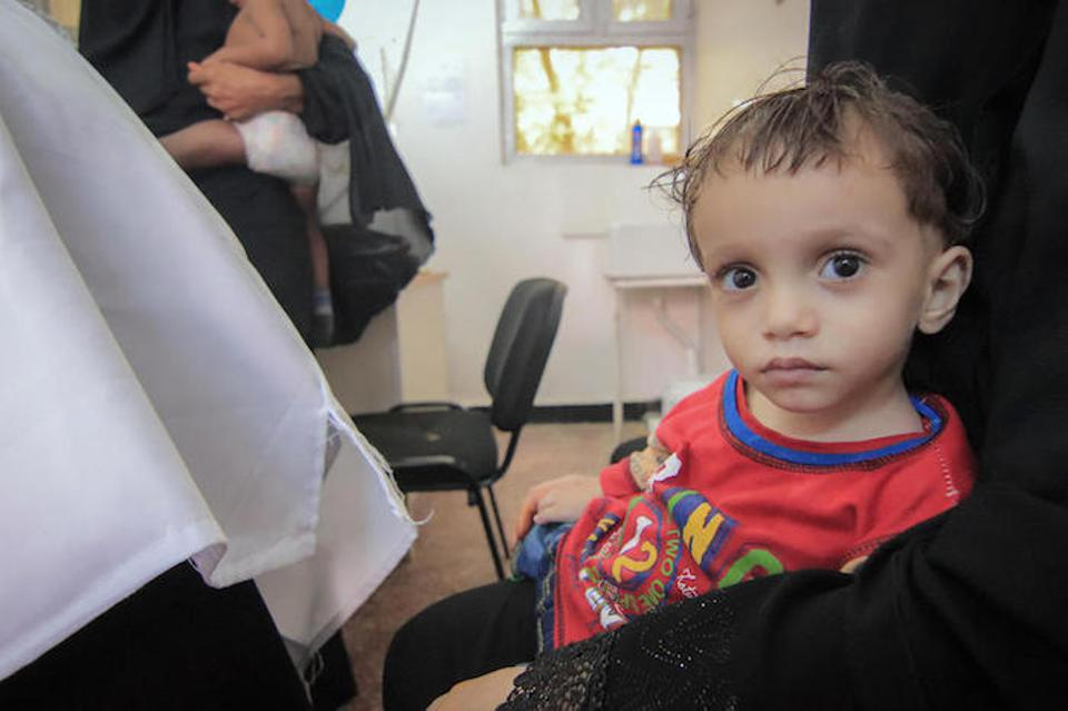 On 25 June 2018 in Yemen, a woman holds a child at the UNICEF-supported Alqatee'a Health Centre in Aden.