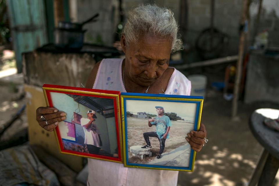 In Honduras, a grandmother holds photos of her 18-year-old grandson, who was murdered with four friends as they sat outside the family home one night in September 2015.