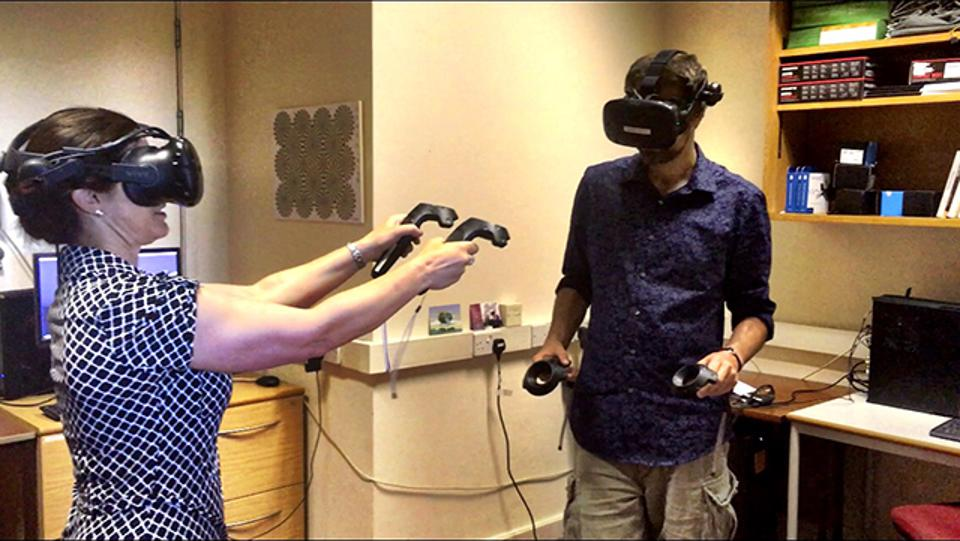 The author, left, and Dr. David Glowacki, cofounder of Interactive Scientific, toss virtual molecules at each other in Bristol Univesity's VR lab.