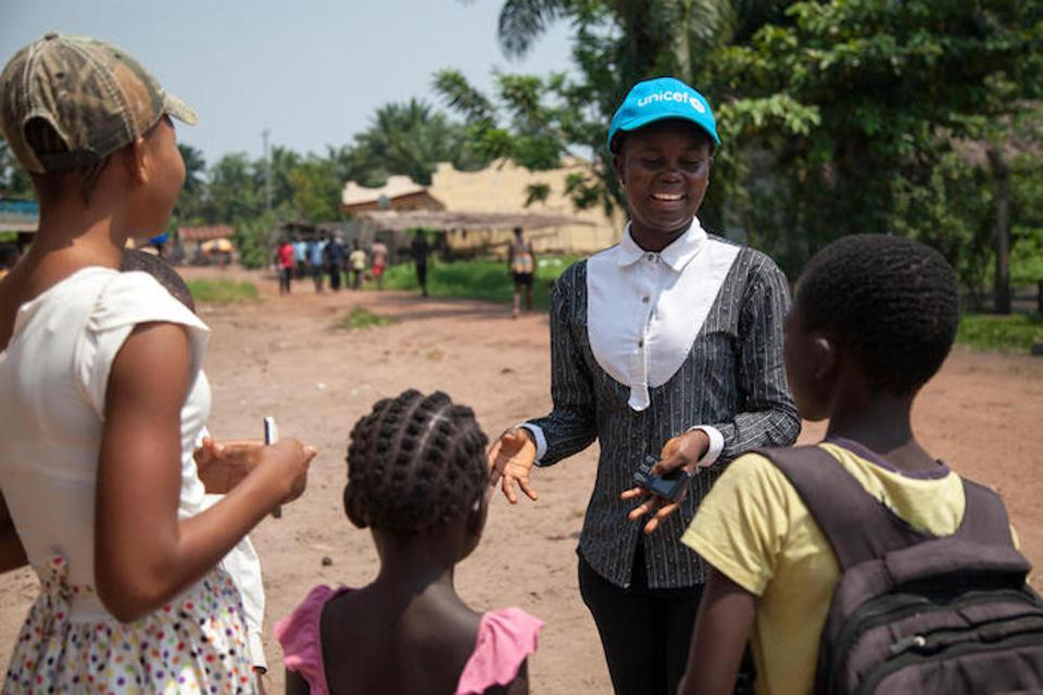 On 6 June 2018 in the Democratic Republic of the Congo, Hornelie Mpiko (in the UNICEF cap), 17, a UNICEF-supported radio reporter/educator, talks to children about Ebola prevention in Mbandaka.