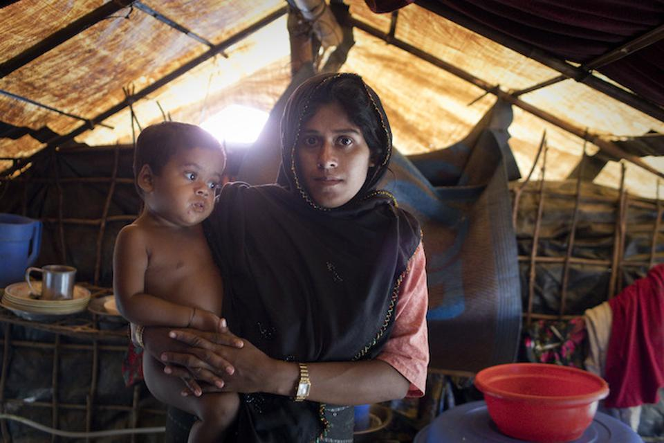 Monsoon rains are flooding homes in the Rohingya refugee camps, complicating humanitarian relief efforts. Kalabana, 25, holds 2-year-old daughter Janna, who was sleeping on a mat one night in June as water poured in, nearly drowning her.