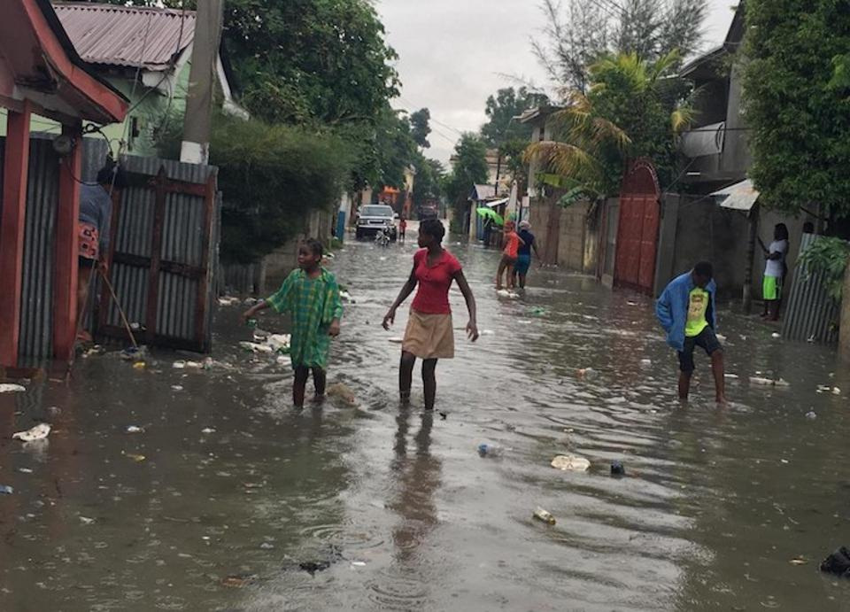 Children and women wade through a flooded street in Hinche, Haiti as Hurricane Irma approaches in 2017.