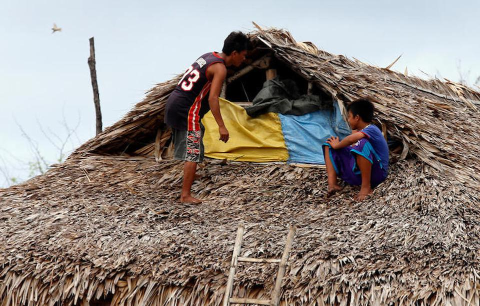 Boys fix the roof of their house in Ilocos Norte Province, northern Luzon on September 14, 2018.