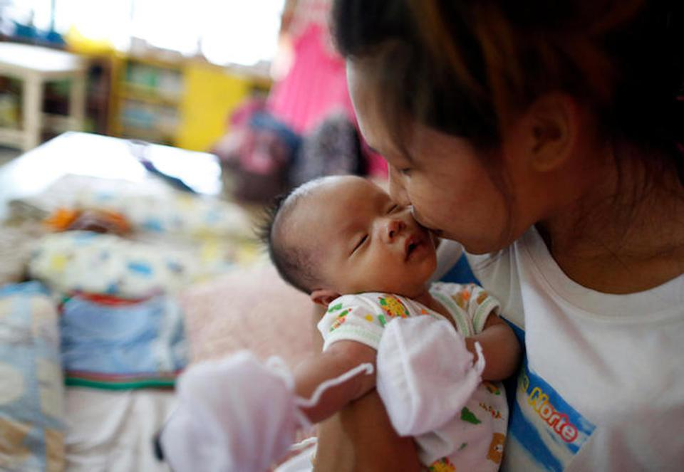 Fleeing Super Typhoon Mangkut, 22-yaer-old Rogeline kisses her 1-month-old daughter, Kristan, at a school turned evacuation center in Luzon's Ilocos Norte Province on September 14, 2018.