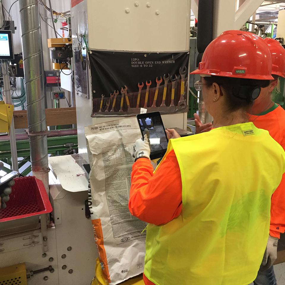 A worker at Corteva Agriscience uses Parsable's app to capture data about a batch of seed corn.