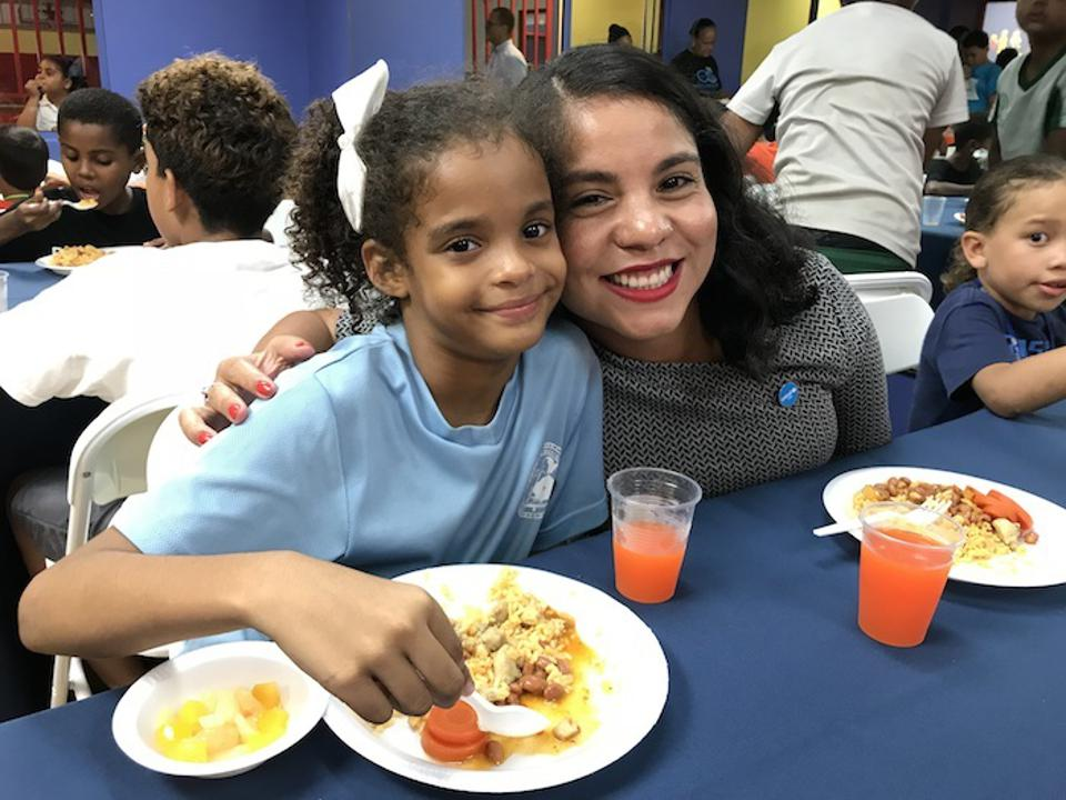 Michelle Centeno, manager of UNICEF USA's Hurricane Maria relief efforts, right, sits with 7-year-old Noyaris, a beneficiary of the new nutrition program launched in September at Boys & Girls Clubs of Puerto Rico with UNICEF USA's support.