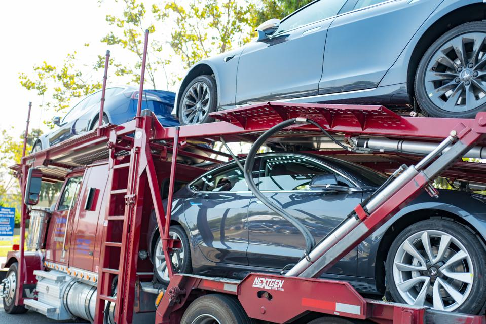 Tesla electric cars, including the Model 3 sedans on a car carrier truck await delivery near the company's in Fremont, California, July 28, 2018. (Smith Collection/Gado/Getty Images)
