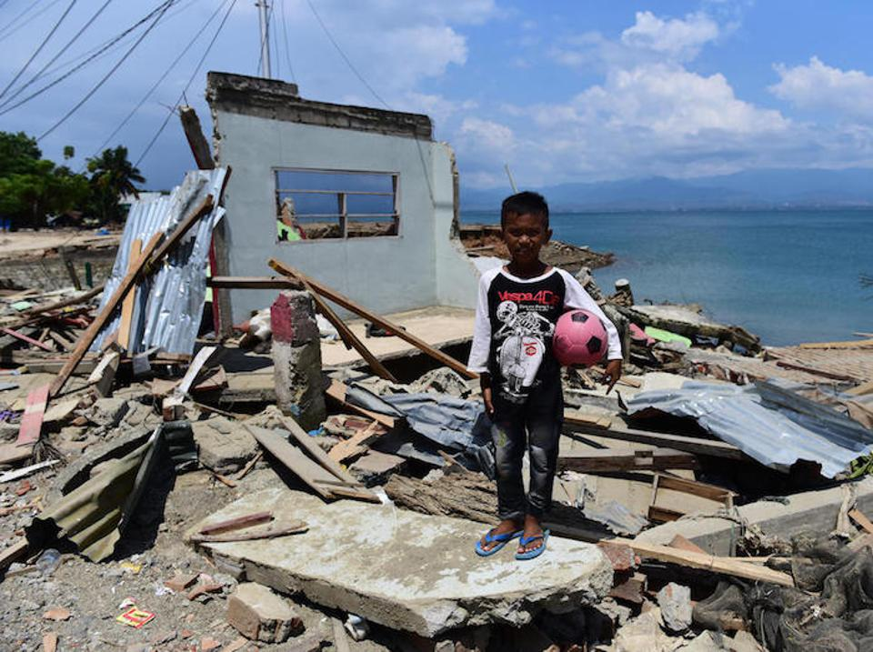 On October 3, 2018, 10-year-old Rido Saputra stands in front of the ruins of his home, destroyed by a tsunami in Donggala Regency, Central Sulawesi, Indonesia.