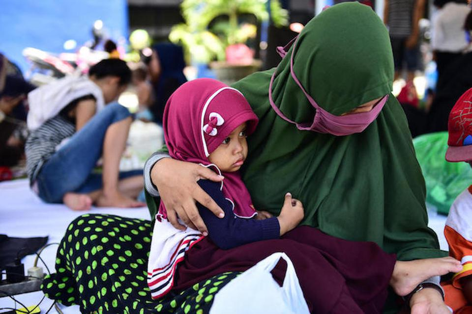 On October 2, 2018 in Indonesia, 2-year-old Fatimah sits on her mother's lap in the evacuation tent yard of the RRI office, East Lolu, Palu City, Central Sulawesi.