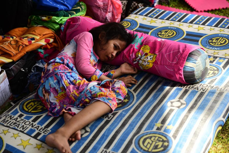 On October 2, 2018, 6-year-old Hilwa cries in the refugee camp in the RRI office as she waits for her mother to return from searching for her missing brother in East Lolu, Palu City, Central Sulawesi.