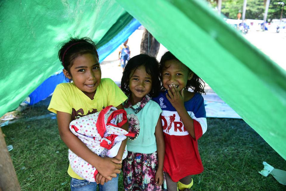 On October 4, children affected by the recent earthquake and tsunami in Palu stand in front of a tent sheltering displaced people in the front yard of the Great Mosque of Palu, Central Sulawesi.