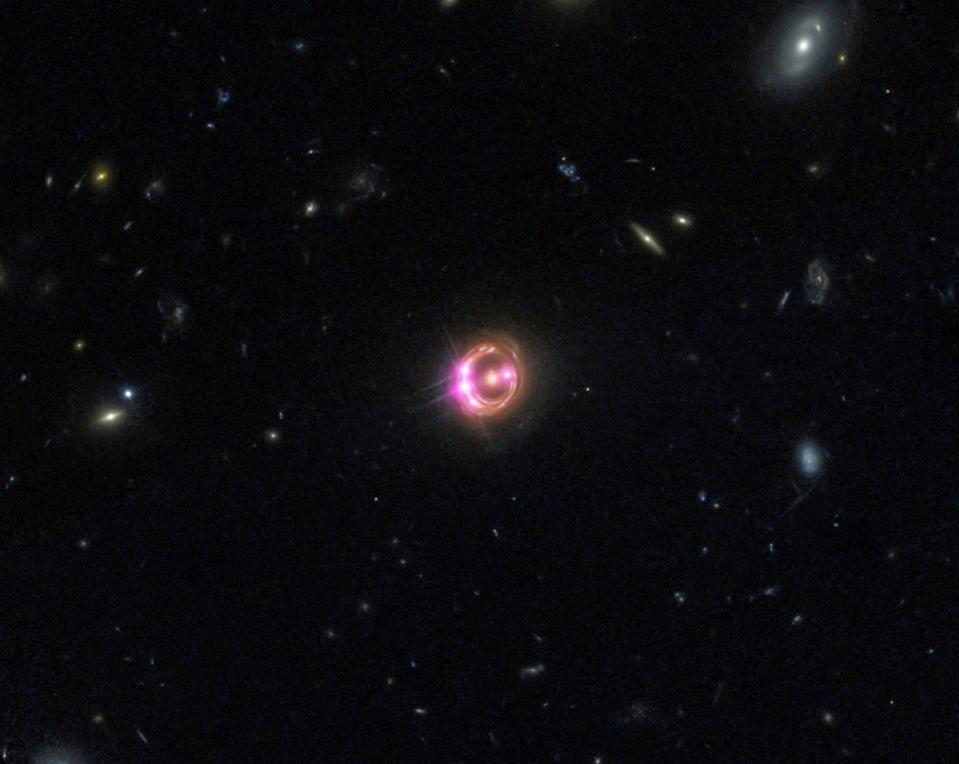 Combination image of quasar RX J1131 (center) taken via NASA's Chandra and Hubble.