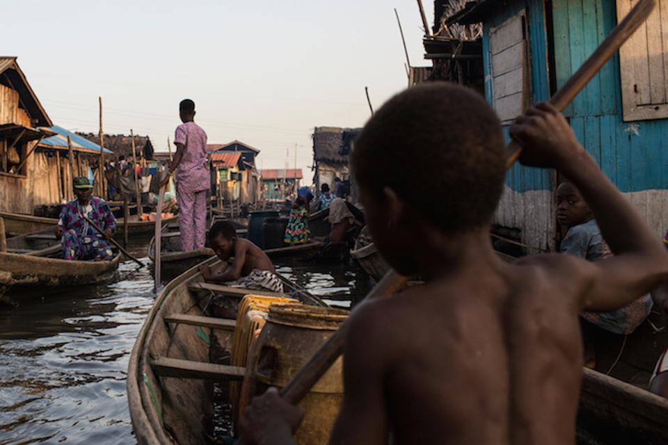 In Lagos, Nigeria, a child navigates the polluted waters of Makoko, a fishing community mostly made up of structures on stilts.