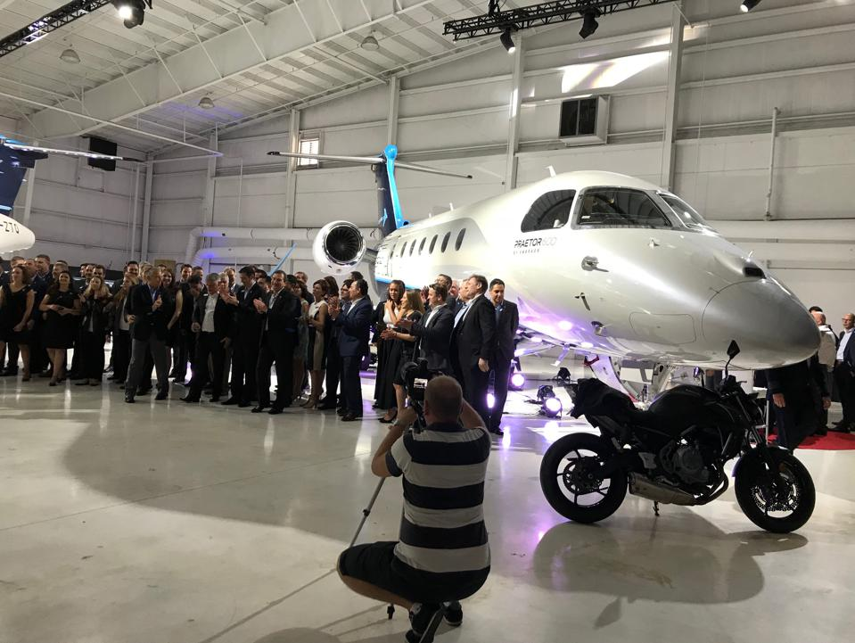 Embraer employees pose for a photo next to the Praetor 600 and the motorcycle CEO Michael Amalfitano ostensibly rode in on for the launch event.