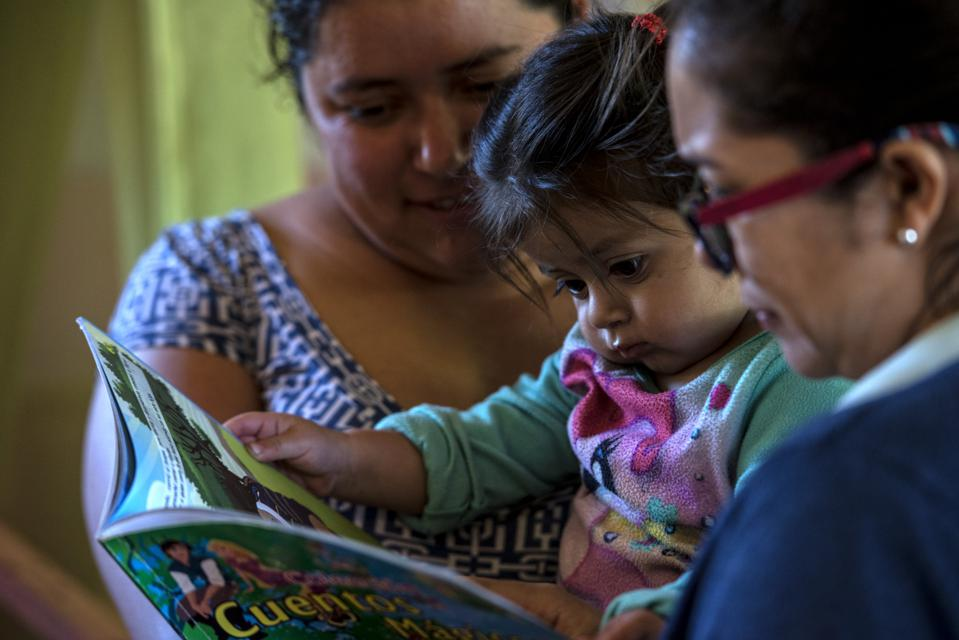 A caregiver and a Whole Child staff member with a child in a care center in El Salvador.