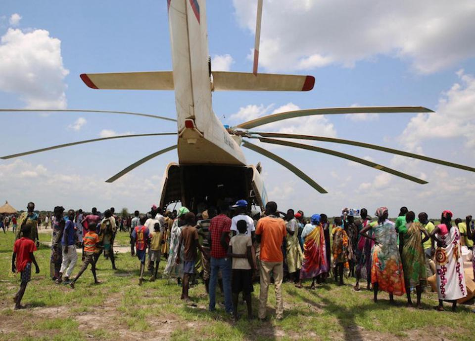 Local volunteers unload supplies from the back of a helicopter in New Fangkak, Jonglei State, South Sudan in July 2018. The supplies included tetanus vaccine and polio drops, Ready-to-Use Therapeutic Food, sanitation and hygiene kits.