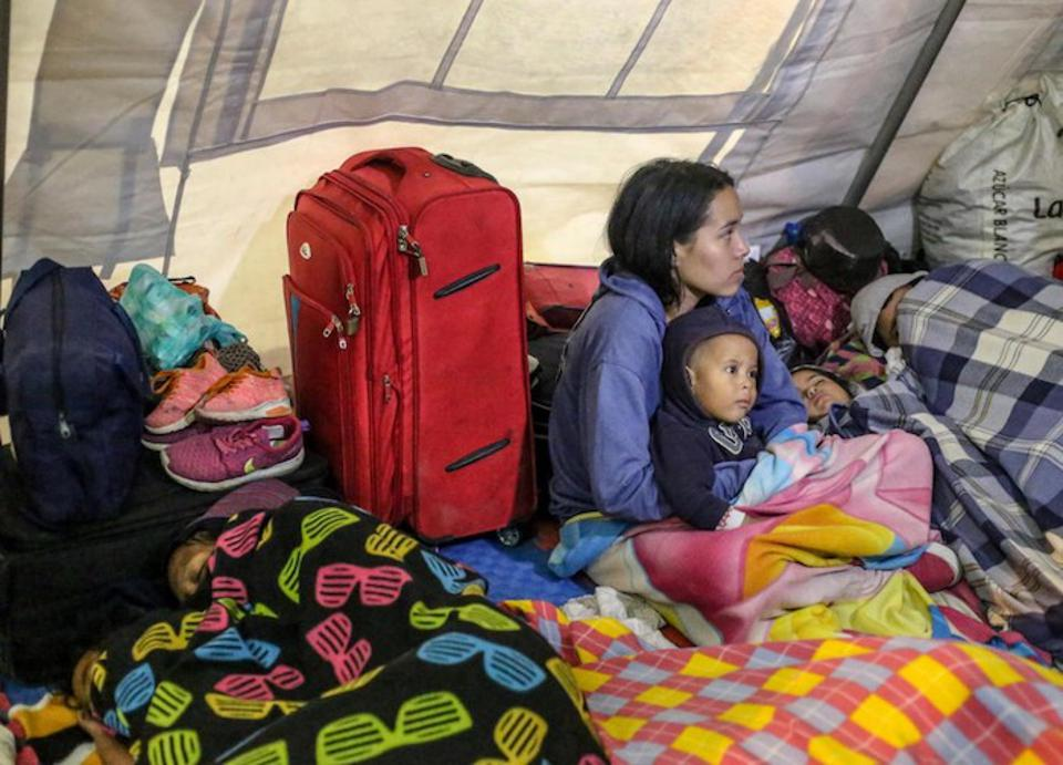 Mothers and children from Venezuela take shelter in a UNICEF temporary rest tent in Rumichaca on the border between Ecuador and Colombia in October 2018.