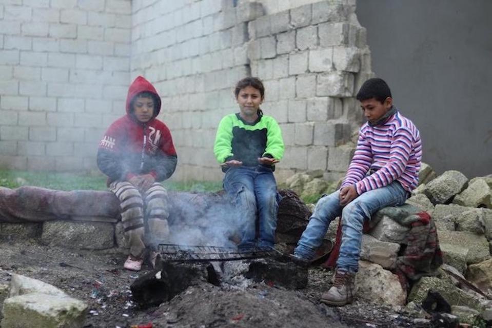 Mohammad, 13 (paling kanan), saudara perempuannya Mehdia yang berusia 9 tahun dan seorang temannya bersiap-siap untuk sekolah di lingkungan Karm Al-Nezha di Aleppo timur.