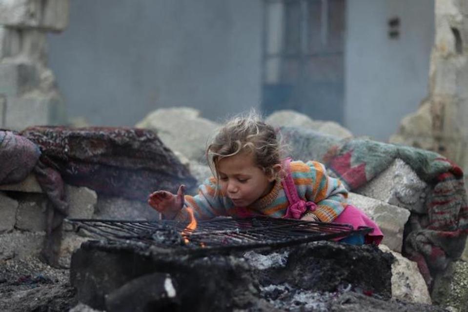 Mountaha, 3, menghangatkan tangannya di atas api di depan gedung tempat keluarganya tinggal di satu kamar.