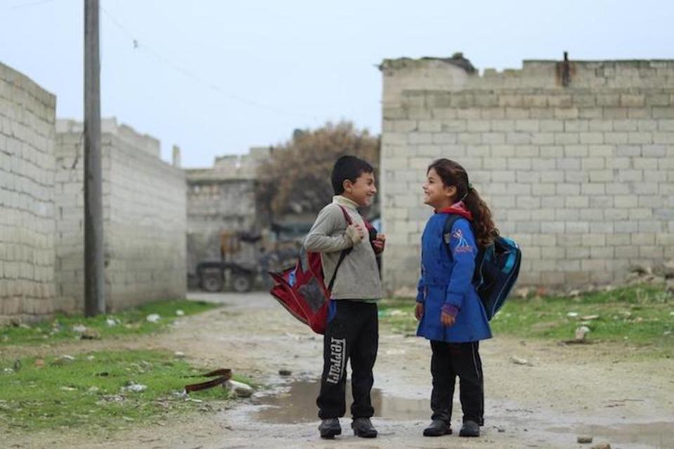 Zahra yang berusia tujuh tahun berjalan ke sekolah bersama seorang teman.