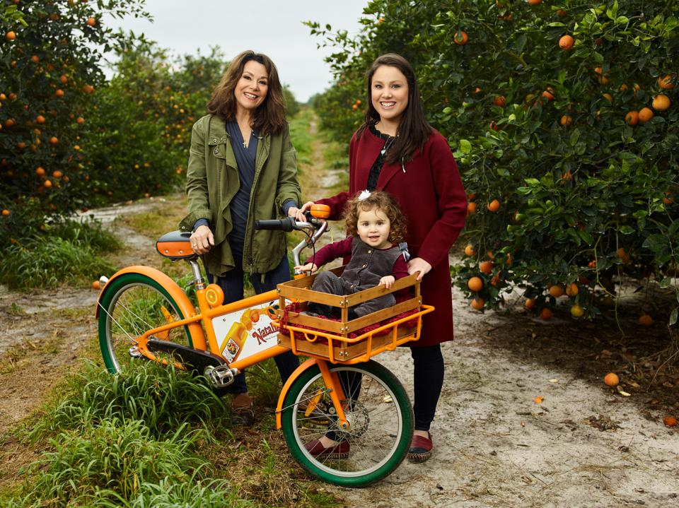 Marygrace Sexton, surrounded by a honeybell orange  grove in southern Florida, with her heir apparent, daughter Natalie, and granddaughter.