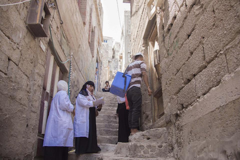 Health workers go door-to-door to provide vaccinations against cholera in Aden, Yemen.